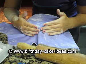 putting fondant on a round cake